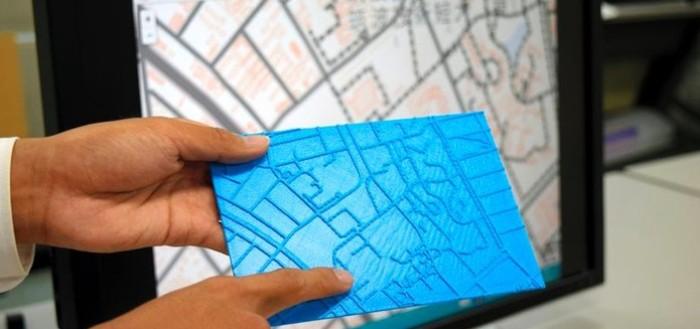 imagem da placa com o mapa de uma área em 3D com um monitor ao fundo mostrando a mesma área no projeto do computador