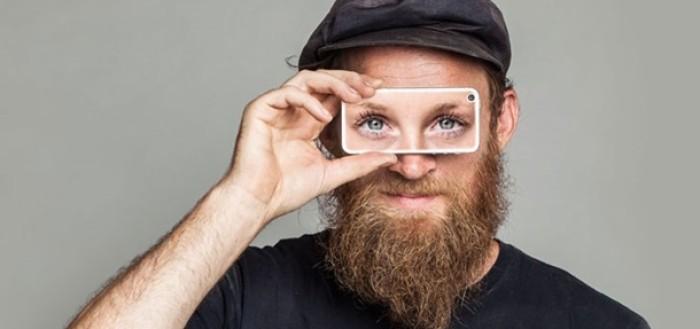 Imagem com um homem de barba segurando um celular na altura dos olhos com outros pares de olhos aparecendo na tela do aparelho
