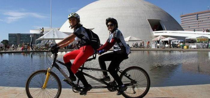 Imagem de um guia e um deficiente visual em uma bicicleta dupla pedalando em Brasília pelo projeto DV na Trilha