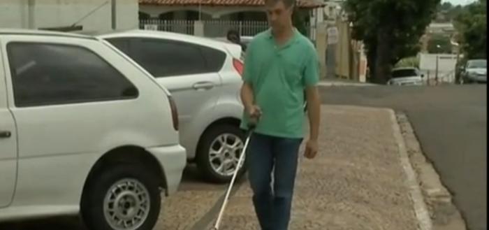 Imagem com Nelson, um cego andando em uma calçada usando a bengala com carros estacionados diagonalmente à sua direita