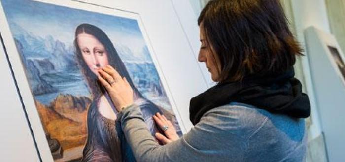 imagem de uma jovem cega tocando o quadro monalis