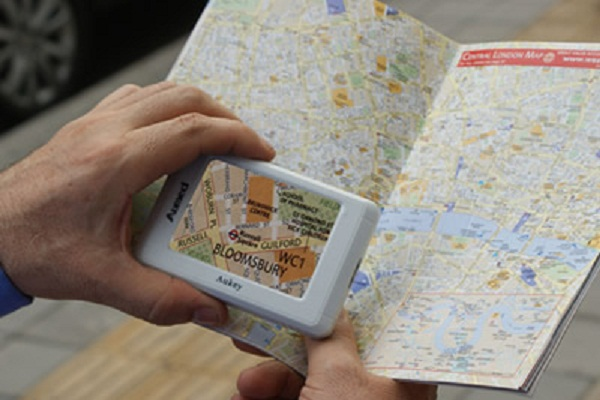 imagem da lupa eletrônica Aukey sendo seguraa por uma mão sobre um livro focalizando um mapa