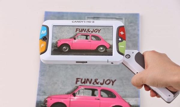 imagem da lupa eletrônica candy com uma pessoa segurando o cabo do aparelho do lado direito focalizando um panfleto de um carro antigo rosa