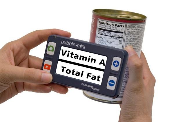 imagem da lupa mini pebble sendo segurada por duas mãos, uma em cada lateral, na tela está sendo focalizada a emblalagem de uma lata de alimentos, mostrando os dizeres vitamina A e total de gordura