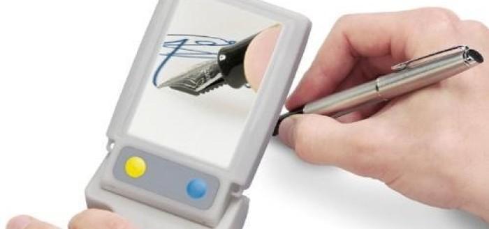 imagem mostrando uma pessoa usando uma lupa eletrônica segurando um lado da lupa na sobre a mão escrevendo com uma caneta bico de pena