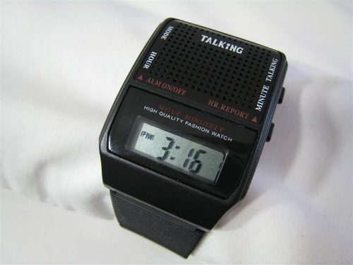 relógio digital modelo clássioco antigo, um quadrad preto com um pequeno visor retangular abaixo que mostra as horas um alto falante logo acima pelo qual é possível ouvir as horas, pulçse4ira de plástico