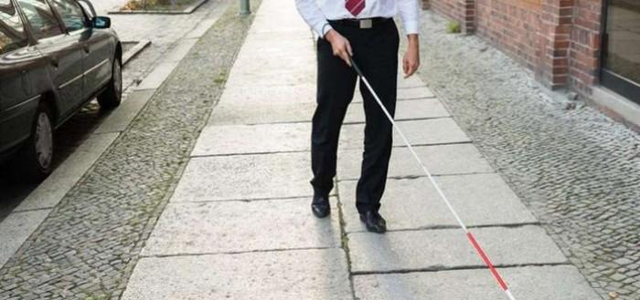 imagem retratando um homem do peito para bai8xo usando gravata, camisa branca e calça social preta caminhado por uma calçada de pedras usando uma bengala