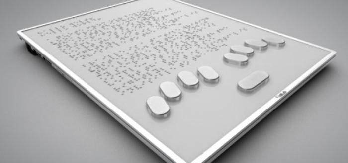 imagem do tablet especial que se parece bastante com um tablet comum, cua tela é toda cinza claro com bordas prateadas, na parte inferior encontram-se nove teclas, quatro do lado esquerdo e quatro do lado direito formando um leve arco com uma tecla maior no centro mais abaixo, acima encontram-se as letras em braille, várias linmhas de conteúdo