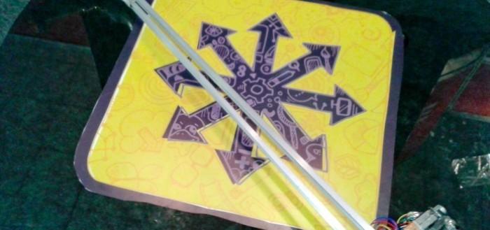 imagem da bengala sobre uma mesa com o desenho de um asterisco grande com setas nas pontas de cada do asterisco