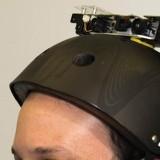 imagem de um rapaz deficiente vvisual vicual com um capacete normalmente utilizado por skatistas com o sensor de movimento kinet usando no xbox preso no topo com um fio indo para as costas, onde há uma mochila