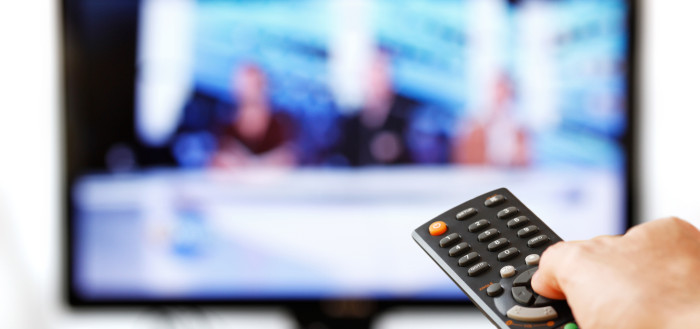 imagem ilustrativa de uma tv de tela plana ao fundo desfocada com uma mão masculina segurando um controle remoto dno canto direito inferior da tela apontando para a televisão