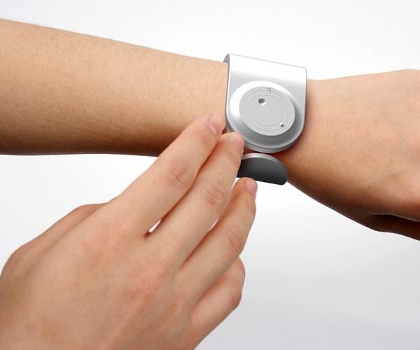 imagem do relógio Rub Feel Know no pulso esquerdo de um homem com o dedo apoiado na face do relógio