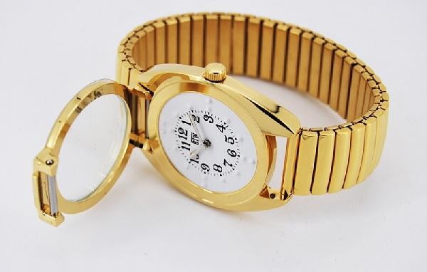d6c26fecaf7 a imagem mostra um relógio dourado posicionado lateralmente em uma mesa com  a talpa aberta mostrando