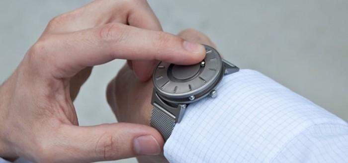 relógio de pulso parra deficientes visuais - imagem mostrando as mãos e o pulso direito de um homem usando um relógio acessível e um dedo da mão esquerda sobre o visor para sentir as horas