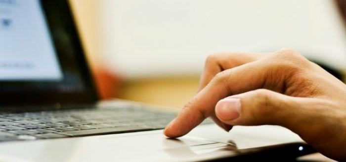 imagem focando na parte do teclado e do pad de um laptop com uma mão sotre a parte do pad touch