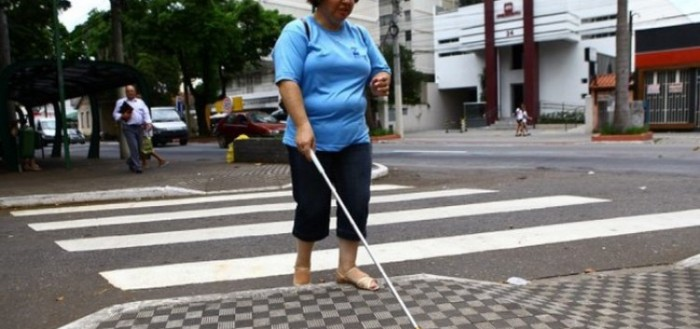 imagem mostrando uma mulher deficiente visual usanco calça escura e blusa azul terminando de atravessar uma rua na faixa de pedestres com sua bengala na mão direita posicionada a sua frente