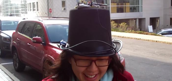 imagem demonstrando o funcionamento do chapéu na rua com uma jovem asiática usando óculos com o chapéu na cabeça andando pela rua