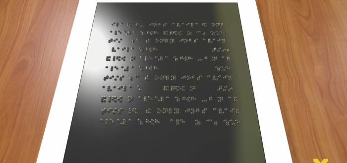 imagem do tablet acessível sobre uma mesa de madeira clara com a tela virada para cima de frete para a câmera com uma luz lateral refletindo na superfície da tela destacando os pontinhos do braille, a tela do dispositivo é excura e a sua borda é branca