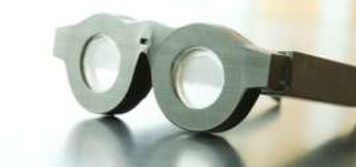 imagem mostrando o óculos inteligente sobre a mesa, o acessório está na diagonal e possui armmação redonda grande e grossa e lentes sutis