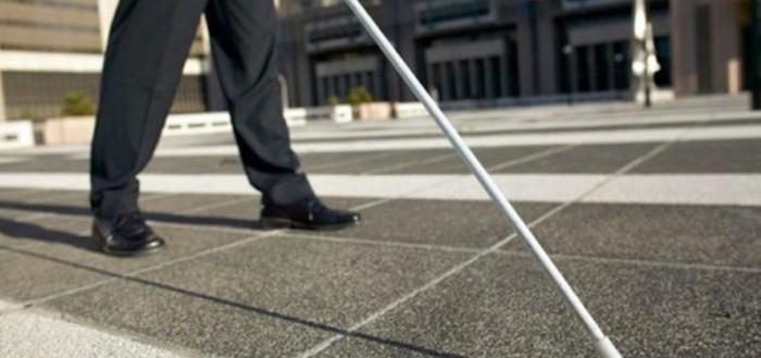 na imagem aparece as pernas de um homem de calça escura andando pela rua com sua bengala branca com ponteira boleada